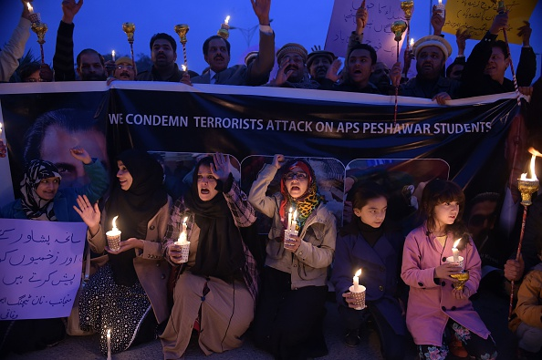 Pakistani lawyers and civil society activists shout slogans as they hold lighted candles during a vigil in Islamabad on December 22, 2014, held for schoolchildren children and teachers killed in an attack by Taliban militants on an army-run school in Peshawar. Pakistan plans to execute around 500 militants in coming weeks, officials said, after the government lifted a moratorium on the death penalty in terror cases following a Taliban school massacre. Six militants have been hanged since December 19 amid rising public anger over the December 16 slaughter in the northwestern city of Peshawar, which left 149 people dead including 133 children. AFP PHOTO/ Aamir QURESHI        (Photo credit should read AAMIR QURESHI/AFP/Getty Images)