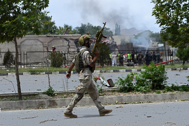 An Afghan security official holds his weapon ready as he walks next to the site of a suicide attack on the Afghan parliament building in Kabul on June 22, 2015. Taliban militants attacked the Afghan parliament on June 22, with gunfire and explosions rocking the building, sending lawmakers running for cover in chaotic scenes relayed live on television.The insurgents tried to storm the complex after triggering a car bomb but were repelled and have taken position in a partially-constructed building nearby, officials said about the ongoing attack. All MPs were safely evacuated after the attack, which came as the Afghan president's nominee for the crucial post of defence minister was to be introduced in parliament. AFP PHOTO / Wakil Kohsar        (Photo credit should read WAKIL KOHSAR/AFP/Getty Images)