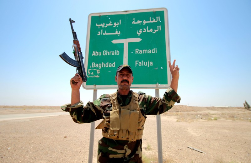 A member of the allied Iraqi forces consisting of the Iraqi army and fighters from the Popular Mobilisation units, poses for a photo in front of a road sign during clashes with Islamic State (IS) group fighters on the outskirts of Fallujah, in Iraq's Anbar province, on August 13, 2015. Anbar, Iraq's largest province, has been rocked by violence since the beginning of 2014, months before the IS jihadist group launched a massive nationwide offensive that saw it conquer swathes of the country. AFP PHOTO / HAIDAR MOHAMMED ALI        (Photo credit should read HAIDAR MOHAMMED ALI/AFP/Getty Images)