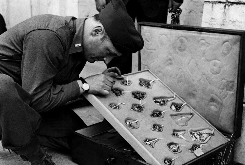 On May 18, 1945, first lieutnant James J. RORIMER, curator at the Metropolitan Museum of New York taking a look at a jewellery collection of the 16th c. stolen by the Nazis from the Rothschild family in Paris. This is in the cellars of the castle of Neuschwanstein. GOERING despoiled families all over Europe to make up a museum. Le 18 mai 1945, le Lieutenant James J. RORIMER, conservateur au Metropolitan Museum de New York examine une collection de bijoux du XVIème siècle dérobée à Paris par les troupes d'occupation à la famille ROTHSCHILD, dans les caves de Neuschwanstein. En spoliant les familles de l'Europe entière, GOERING avait pour but de se constituer un musée.