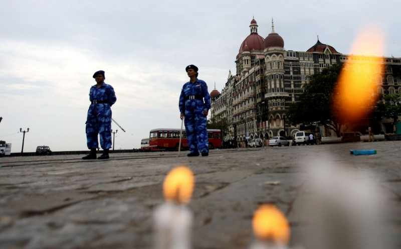 Indian paramilitary forces stand guard as candles placed by people in memory of those killed by militants from diferent walks of life burn in front of the Taj Mahal hotel in Mumbai on November 30, 2008. The attacks on Mumbai have again highlighted the lack of coherence in India's counter terrorism strategy, its underfunded intelligence services and its poor rapid response networks, analysts say.  AFP PHOTO/ Sajjad HUSSAIN        (Photo credit should read SAJJAD HUSSAIN/AFP/Getty Images)