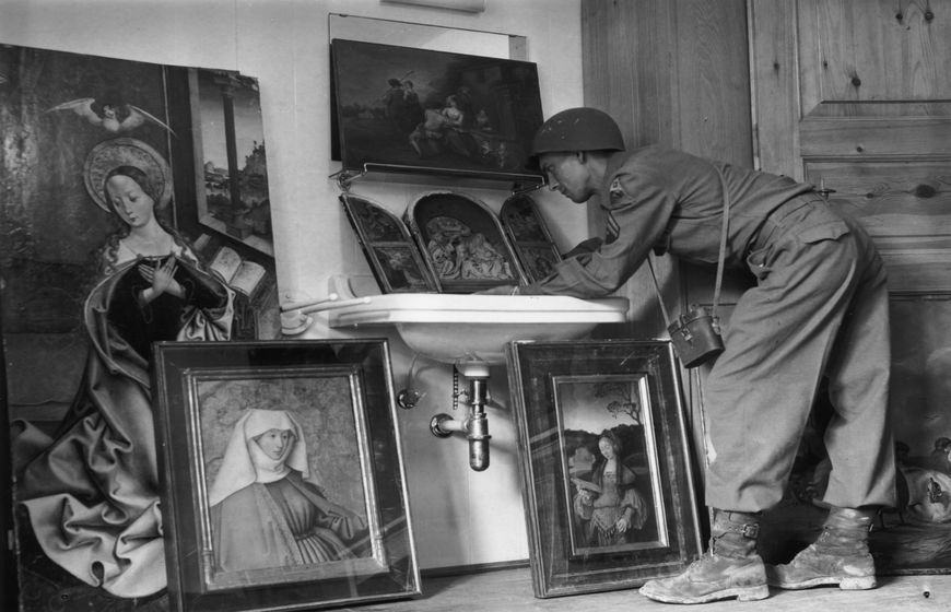 May 1945:  American servicemen view art treasures on show at a former Luftwaffe barracks near Konigsee. Priceless paintings looted from all parts of Europe under orders from Hermann Goering.  (Photo by Horace Abrahams/Keystone/Getty Images)