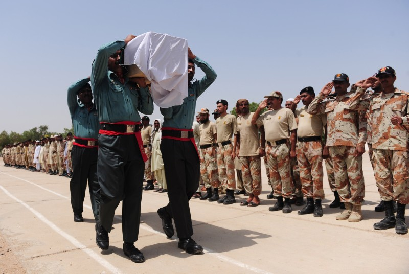 Pakistani Rangers carry the coffin of a colleague killed during an assault by militants on Karachi airport during funeral ceremonies in Karachi on June 9, 2014. Twenty-eight people were killed as Pakistan's military fought an all-night battle with Taliban gunmen who besieged Karachi airport armed with rocket launchers and suicide vests, leaving a nascent peace process in tatters. Ten militants were among the dead, officials said, as Pakistan's biggest city witnessed a return of the kind of spectacular offensive waged before by the Tehreek-e-Taliban Pakistan (TTP) during an insurgency that has claimed thousands of lives since 2007. AFP PHOTO/Rizwan TABASSUM        (Photo credit should read RIZWAN TABASSUM/AFP/Getty Images)