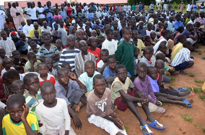 "A picture taken on August 21, 2014 shows Internally Displaced People (IDP) sitting in Mubi camp in Nigeria's northeastern Adamawa State. Mostly women and children, the IDPs in Mubi fled their homes in Gwoza, Borno State, to neighbouring Adamawa State following incessant attacks by Islamists insurgents Boko Haram. Nearly 11,500 people from one town in northeast Nigeria are receiving emergency aid after fleeing Boko Haram militants, the country's main relief agency said on on August 21. The National Emergency Management Agency (NEMA) said 11,442 men, women and children from Gwoza in Borno state had been registered at two facilities for displaced people in neighbouring Adamawa state. The Islamists took over Gwoza, which lies near the border with Cameroon, on August 7 and NEMA said the town was ""still under siege"".  AFP PHOTO/ OLATUNJI OMIRIN        (Photo credit should read OLATUNJI OMIRIN/AFP/Getty Images)"