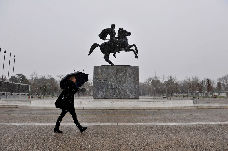 A woman walks past the statue of Alexander the Great under the shelter of her umbrella as snow falls in Thessaloniki on February 9, 2015. A number of roads in northern Greece were closed after temperatures dropped below zero and snow fell in many parts.  AFP PHOTO /Sakis Mitrolidis        (Photo credit should read SAKIS MITROLIDIS/AFP/Getty Images)