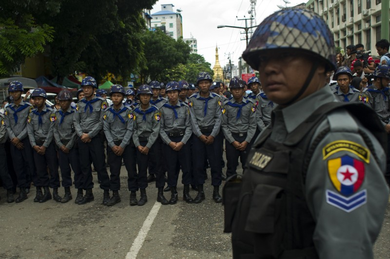Police hold positions as they face off against student protesters during a demonstration against unelected soldiers who make up a quarter of parliamentary seats, in Yangon on June 30, 2015. Angry crowds scuffled with hundreds of police in downtown Yangon June 30 in a protest against the Myanmar army's veto on constitutional change, blamed for the defeat last week of a charter reform bill backed by Aung San Suu Kyi. AFP PHOTO / YE AUNG THU        (Photo credit should read Ye Aung Thu/AFP/Getty Images)