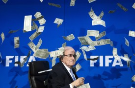 FIFA president Sepp Blatter looks on as fake dollar notes fly around him, thrown by a British comedian during a press conference at the FIFA world-body headquarter's on July 20, 2015 in Zurich. The 79-year-old Swiss official looked shaken as the notes thrown by Simon Brodkin, stagename Lee Nelson, fluttered around him in a conference hall at the FIFA headquarters. Brodkin was taken away in a Swiss police car after the stunt. AFP PHOTO / FABRICE COFFRINI / AFP / FABRICE COFFRINI        (Photo credit should read FABRICE COFFRINI/AFP/Getty Images)