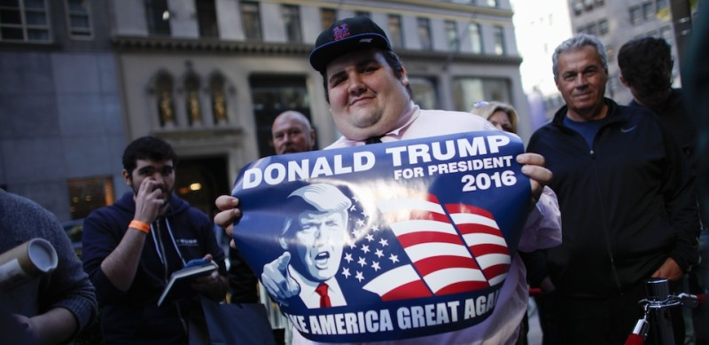 """A supporter of Republican presidential hopeful Donald Trump waits in line the launch event for Trump's new book """"Crippled America: How to Make America Great Again"""" outside the Trump Tower on November 3, 2015 in New York.  Donald Trump published a book about the ills of America to another media frenzy Tuesday, signing copies for fans, insulting his rivals on the campaign trail and telling Americans to elect him president. """"Crippled America: How to Make America Great Again,"""" offers the everyday reader his take on the problems facing the country and why they should elect him to the White House to fix them. AFP PHOTO/Kena Betancur        (Photo credit should read KENA BETANCUR/AFP/Getty Images)"""