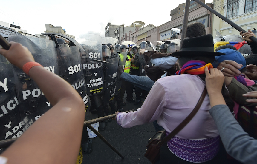Demonstrators face policemen during a protest against a constitutional amendment which would allow indefinite re-election in front of a line of riot policemen in Quito on December 3, 2015. The pro-government majority of the Congress is ready to approve indefinite re-election since 2021 in Ecuador. AFP PHOTO / RODRIGO BUENDIA / AFP / RODRIGO BUENDIA        (Photo credit should read RODRIGO BUENDIA/AFP/Getty Images)