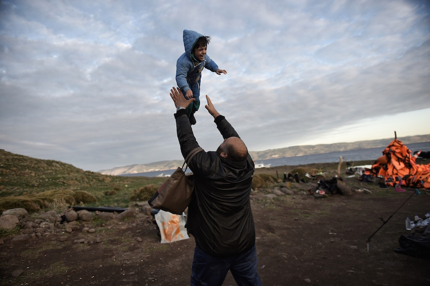 A man throws his boy in the air after arriving with other refugees and migrants at the Greek island of Lesbos after crossing the Aegean sea from Turkey on December 4, 2015.  / AFP / ARIS MESSINIS        (Photo credit should read ARIS MESSINIS/AFP/Getty Images)