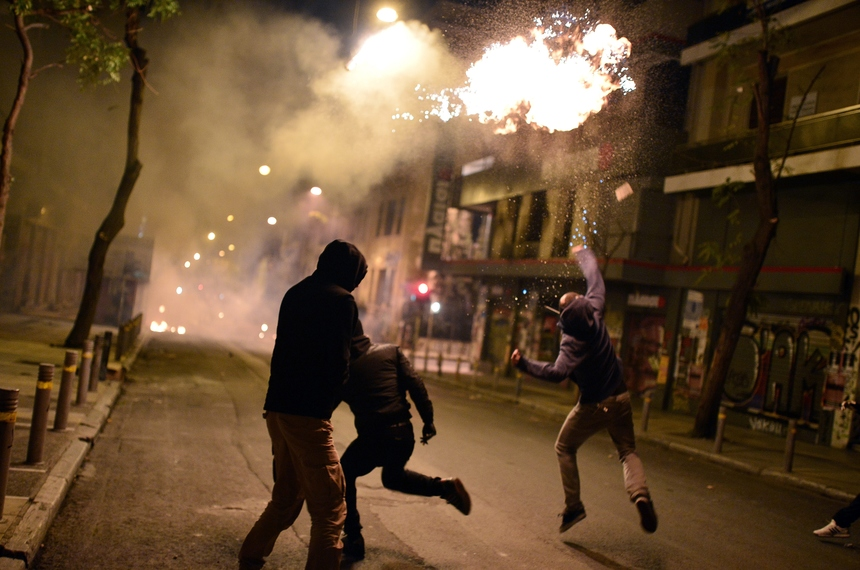 TOPSHOT - A youth throws a molotov cocktail towards Greek riot police during clashes in Athens on December 6, 2015. Anarchists turned part of central Athens into a battleground during a march to mark the seventh anniversary of the fatal shooting of 15-year-old boy by police. Alexis Grigoropoulos was shot dead by police on December 6, 2008 sparking weeks of riots. / AFP / LOUISA GOULIAMAKI        (Photo credit should read LOUISA GOULIAMAKI/AFP/Getty Images)