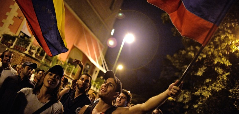 Venezuelan opposition supporters celebrate the results of the legislative election in Caracas, on the early morning December 7, 2015. Venezuela's opposition won --at least--a majority of 99 out of 167 seats in the state legislature, electoral authorities said Monday, the first such shift in power in congress in 16 years.   AFP PHOTO/LUIS ROBAYO / AFP / LUIS ROBAYO        (Photo credit should read LUIS ROBAYO/AFP/Getty Images)