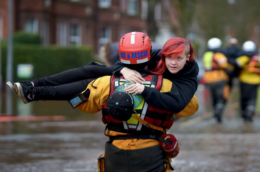 CARLISLE, ENGLAND - DECEMBER 07:  A member of the rescue team carries a young woman to safety through the flood water as they continue to to evacuate homes after Storm Desmond caused flooding on December 7, 2015 in Carlisle, England. Storm Desmond has brought severe disruption to areas of northern England with dozens of flood warnings remaining in place throughout the country. (Photo by Jeff J Mitchell/Getty Images)