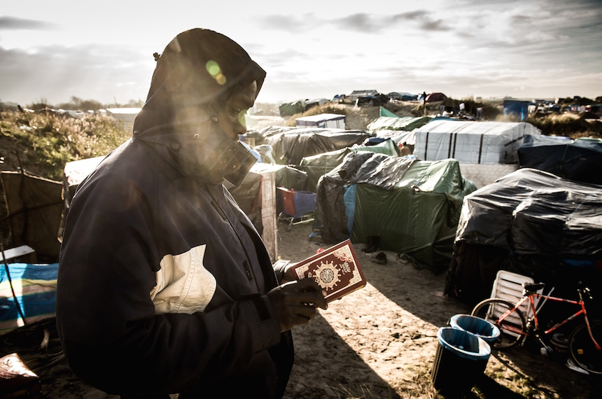 "TOPSHOT - A man from Sudan reads the Koran at the migrant camp known as the ""Jungle"" in Calais on December 7, 2015. / AFP / PHILIPPE HUGUEN        (Photo credit should read PHILIPPE HUGUEN/AFP/Getty Images)"