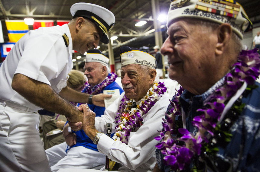 HONOLULU, HI -  MONDAY, DECEMBER 07:  U.S. Navy Captain Mark Manfredi greets Pearl Harbor Survivor Delton E. Whaling (2nd R) before the start of a memorial service marking the 74th Anniversary of the attack on the U.S. naval base at Pearl Harbor December 07, 2015 on the island of Oahu at the Kilo Pier at Joint Base Pearl Harbor-Hickam in Honolulu, Hawaii. In 1941 the Japanese attacked Pearl Harbor, killing thousands and launchingthe U.S. inot WWII.  (Photo by Kent Nishimura/Getty Images)