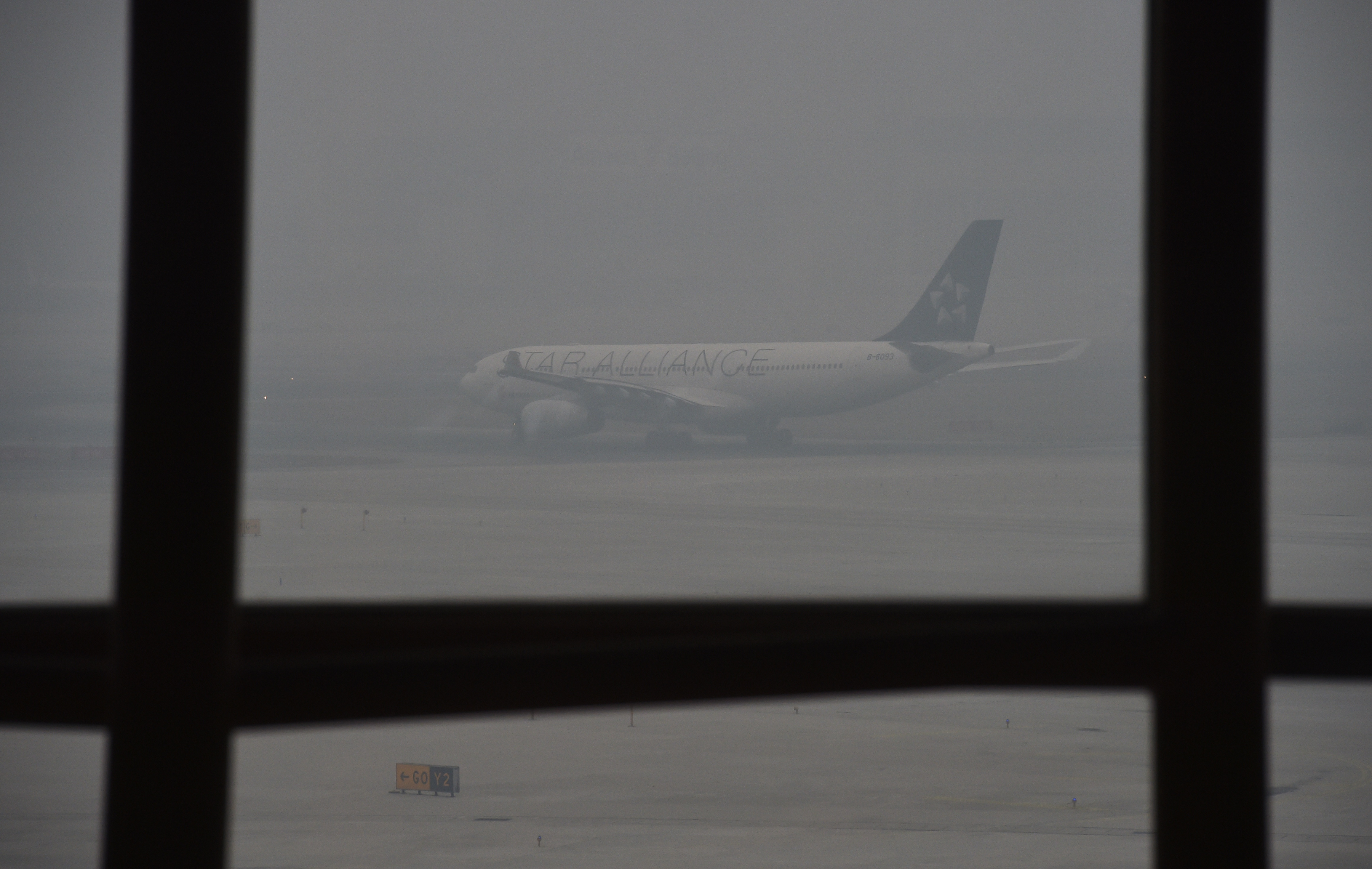 A plane waits to take off on a day of heavy pollution at the airport in Beijing on December 8, 2015. Half of Beijing's private cars were ordered off the streets on December 8 and many construction sites and schools were closed under the Chinese capital's first-ever red alert for pollution. AFP PHOTO / GREG BAKER / AFP / GREG BAKER (Photo credit should read GREG BAKER/AFP/Getty Images)