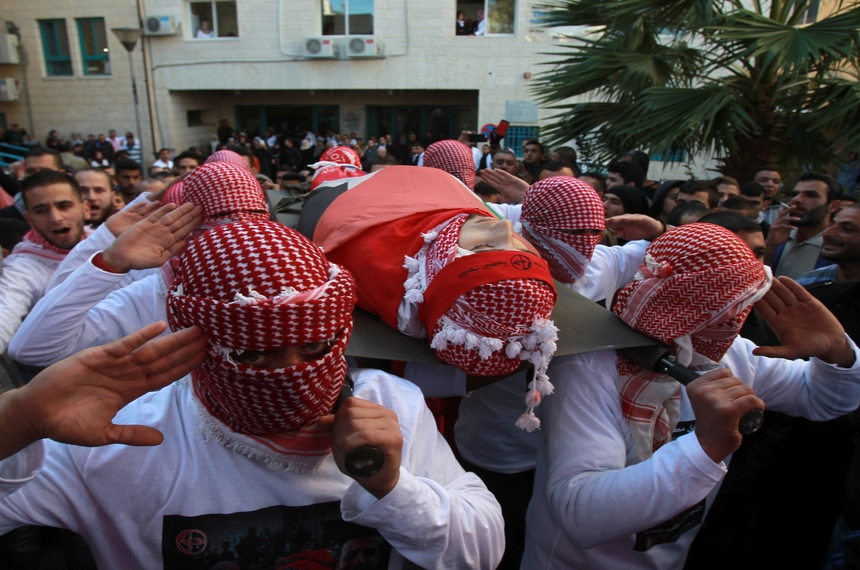 Mourners carry the body of Malek Shahin, a 19 year-old Palestinian who was killed in clashes with Israeli security forces, during his funeral procession in the Dheisheh refugee camp near the West Bank town of Bethlehem on December 08, 2015. Israeli soldiers shot Shahin dead as clashes broke out during an early morning raid at the refugee camp, Palestinian medics and the Israeli army said. AFP PHOTO/ MUSA AL SHAER / AFP / MUSA AL-SHAER        (Photo credit should read MUSA AL-SHAER/AFP/Getty Images)