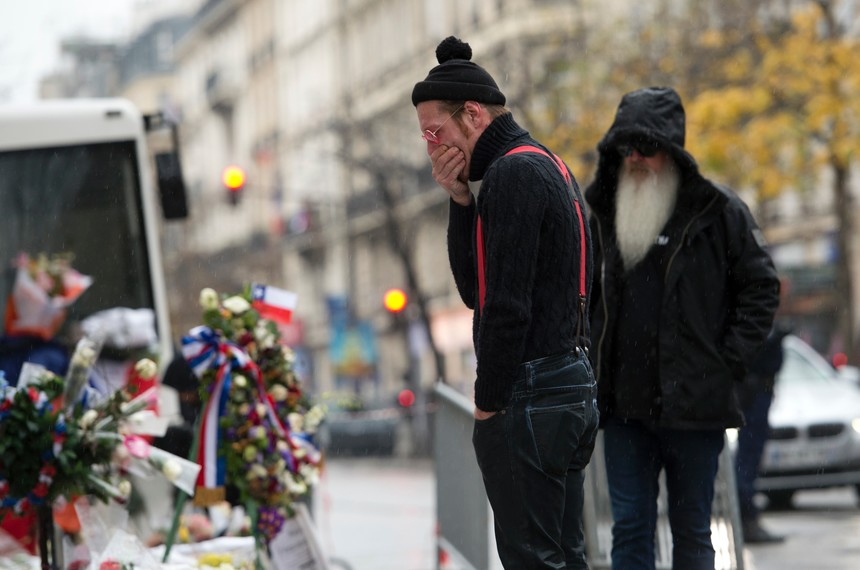 TOPSHOT - Singer of the US rock group Eagles of Death metal Jesse Hughes (L) and guitarist Dave Catching pay tribute to the victims of the November 13 Paris terrorist attacks at a makeshift memorial in front of the Bataclan concert hall on December 8, 2015 in Paris.  The Eagles of Death Metal band returned to the Bataclan concert hall in Paris, nearly a month after they survived a jihadist attack there in which 90 people died. / AFP / MIGUEL MEDINA        (Photo credit should read MIGUEL MEDINA/AFP/Getty Images)