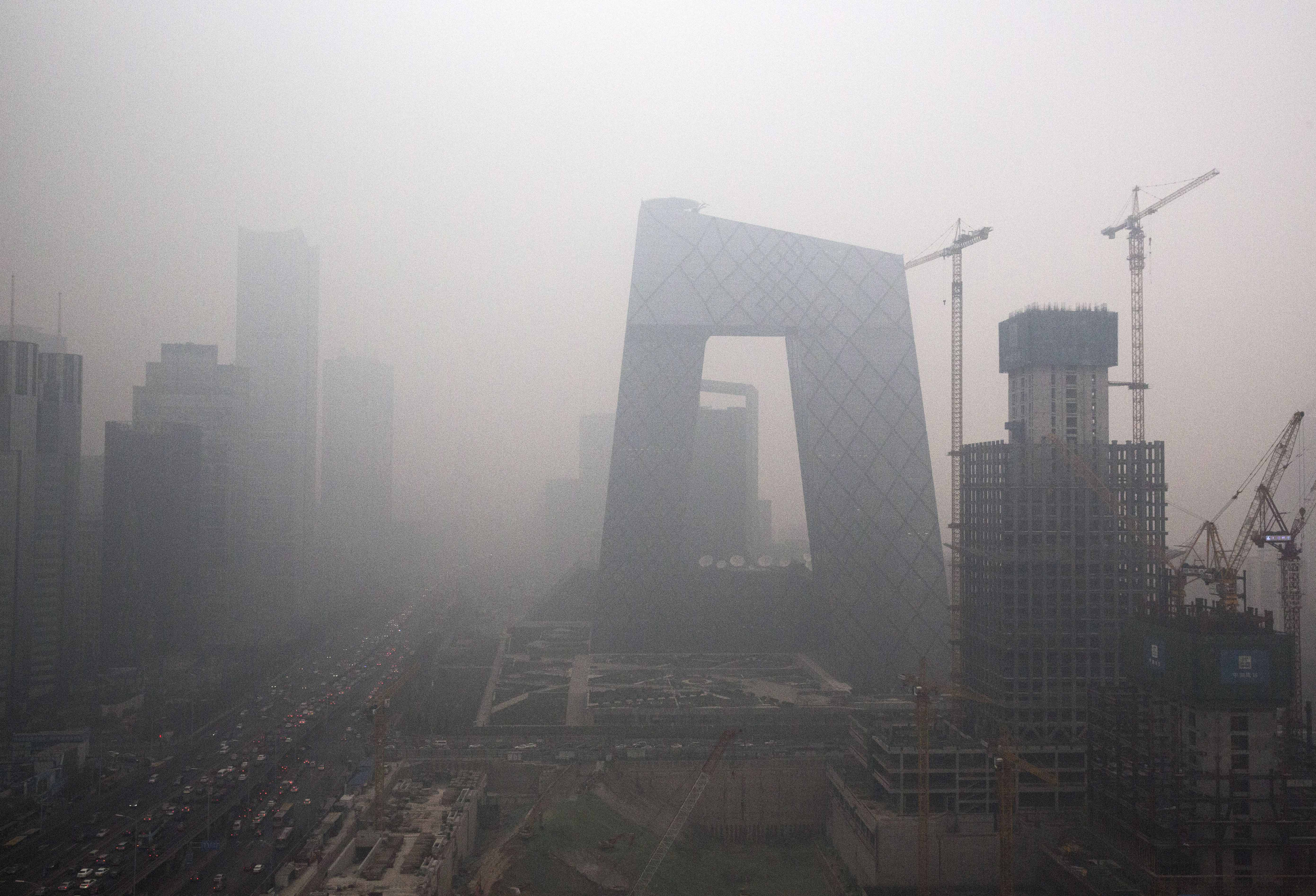 """BEIJING, CHINA - DECEMBER 08: The Central Business District is seen in heavy smog on December 8, 2015 in Beijing, China. The Beijing government issued a """"red alert"""" for the first time since new standards were introduced earlier this year as the city and many parts of northern China were shrouded in heavy pollution. Levels of PM 2.5, considered the most hazardous, crossed 400 units in Beijing, lower than last week, but still nearly 20 times the acceptable standard set by the World Health Organization. The governments of more than 190 countries are meeting in Paris to set targets on reducing carbon emissions in an attempt to forge a new global agreement on climate change. (Photo by Kevin Frayer/Getty Images)"""
