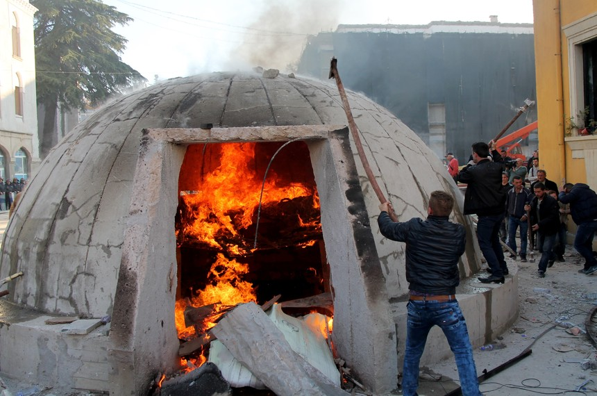 TOPSHOT - Opposition protesters destroy a bunker installed as an artwork near the Interior ministry  during a rally organized by the opposition Democratic Party to demand the resignation of the government, in Tirana, on December 8, 2015, on the day that marks the 25th anniversary of the student protests that led to the toppling of the last communist regime in Europe in 1990.  The bunker bears a striking resemblance to the 700,000 circular bunkers built across Albania during the 40-year rule of dictator Enver Hoxha, who feared attacks from both the Soviet Union and the West. That history has left some people concerned that the new addition is a reflection of growing nostalgia for the communist era. / AFP / GENT SHKULLAKU        (Photo credit should read GENT SHKULLAKU/AFP/Getty Images)
