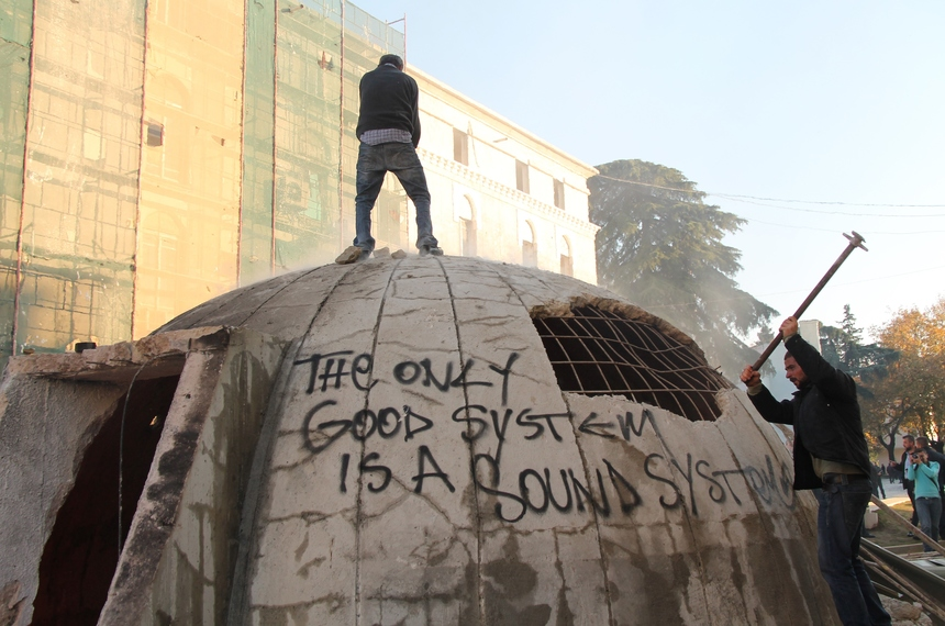 Opposition protesters destroy a bunker installed as an artwork near the Interior ministry  during a rally organized by the opposition Democratic Party to demand the resignation of the government, in Tirana, on December 8, 2015, on the day that marks the 25th anniversary of the student protests that led to the toppling of the last communist regime in Europe in 1990.  The bunker bears a striking resemblance to the 700,000 circular bunkers built across Albania during the 40-year rule of dictator Enver Hoxha, who feared attacks from both the Soviet Union and the West. That history has left some people concerned that the new addition is a reflection of growing nostalgia for the communist era. / AFP / GENT SHKULLAKU        (Photo credit should read GENT SHKULLAKU/AFP/Getty Images)