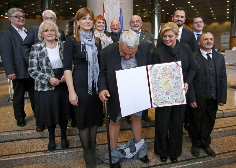 Croatia's leading rights group chief Ivan Zvonimir Cicak's (C) looks down after his trousers fell down while posing for a photo with Croatian President Kolinda Grabar-Kitarovic (2nd R) on December 8, 2015 in Zagreb. Croatian Helsinki Committee president Ivan Zvonimir Cicak's trousers suddenly slipped to his ankles while he was posing in the front row of a group photo along with Croatian President Kolinda Grabar-Kitarovic, during a photo session of an event marking the forthcoming international human rights day. / AFP / STRINGER        (Photo credit should read STRINGER/AFP/Getty Images)
