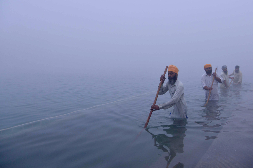 Indian Sikh devotees clean the holy sarover (water tank) during dense fog at the Golden Temple in Amritsar on December 9, 2015.    AFP PHOTO/ NARINDER NANU / AFP / NARINDER NANU        (Photo credit should read NARINDER NANU/AFP/Getty Images)