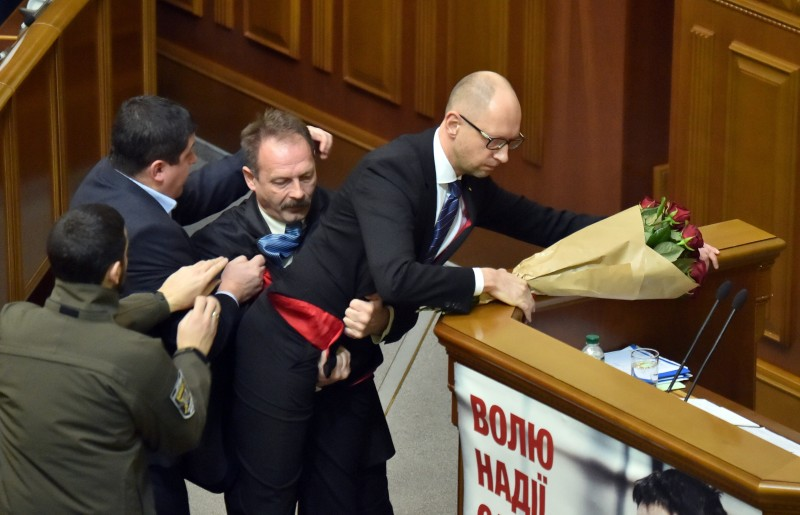 TOPSHOT - A deputy from the Ukrainian President's political party attacks Ukrainian Prime minister Arseniy Yatsenyuk (R) during the annual report of the government in the Ukrainian Parliament on December 11,2015. / AFP / Sergei SUPINSKY        (Photo credit should read SERGEI SUPINSKY/AFP/Getty Images)