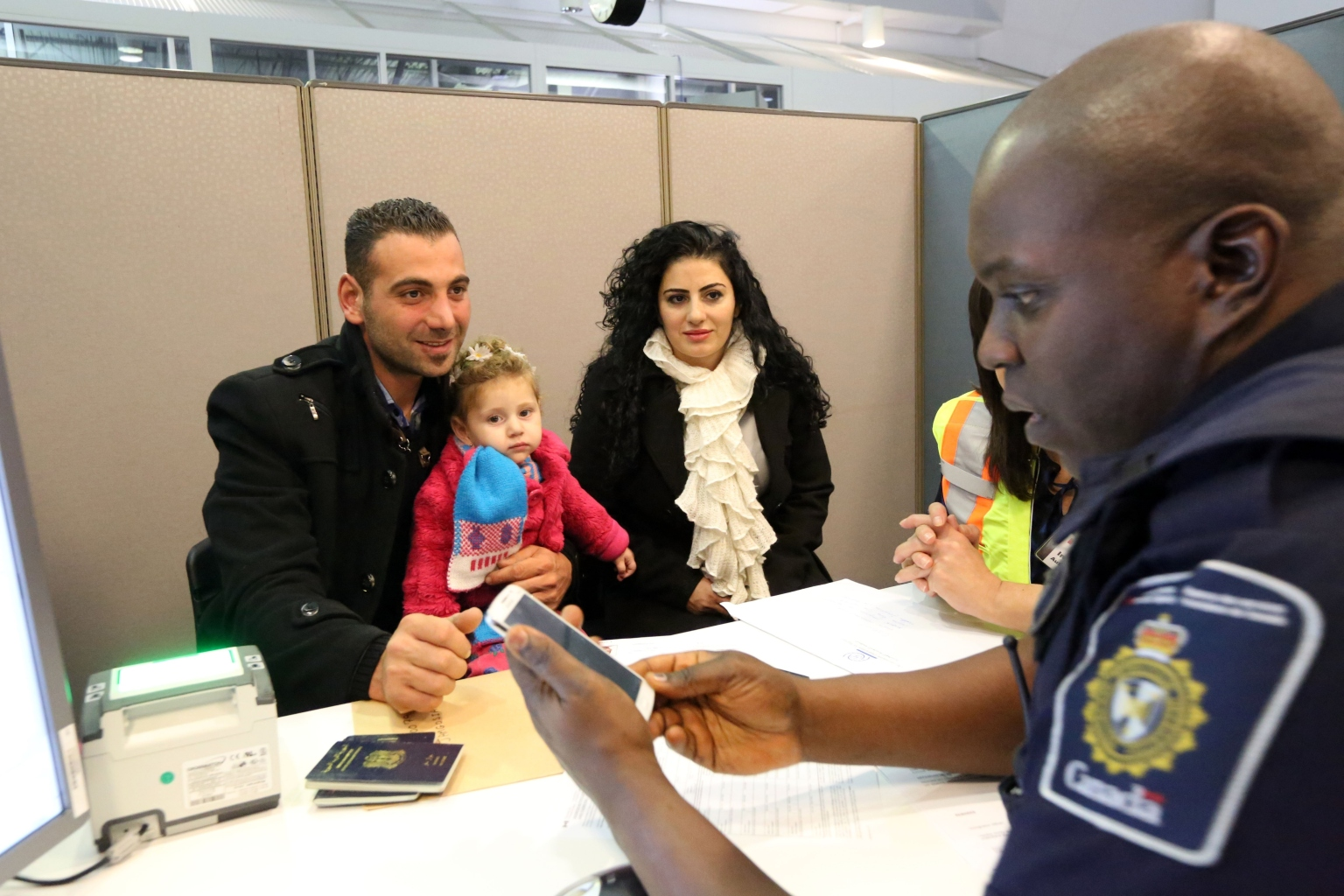 TORONTO, CANADA - DECEMBER 11: Border Services Officer Boakye-Cotie processes a Syrian refugee family at Toronto Pearson International Airport on December 11, 2015. (Photo by Kenneth Allan/Canada Border Services Agency/Pool/Anadolu Agency/Getty Images)