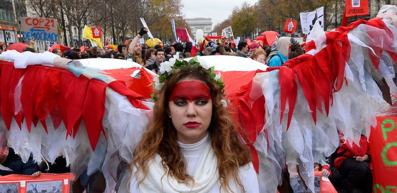 An activist joins others to form a giant red line during a demonstration near the Arc de Triomphe at the Avenue de la Grande armee boulevard in Paris on December 12, 2015, as a proposed 195-nation accord to curb emissions of the heat-trapping gases that threaten to wreak havoc on Earth's climate system is to be presented at the United Nations conference on climate change COP21 in Le Bourget, on the outskirts of Paris.  AFP PHOTO / ALAIN JOCARD / AFP / ALAIN JOCARD        (Photo credit should read ALAIN JOCARD/AFP/Getty Images)