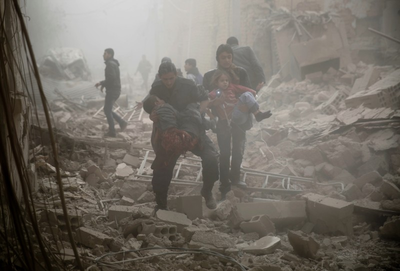 TOPSHOT - GRAPHIC CONTENT Syrians evacuate victims following air strikes on the town of Douma in the eastern Ghouta region, a rebel stronghold east of the capital Damascus, on December 13, 2015. At least 28 civilians were killed in heavy bombardment of the besieged Syrian rebel stronghold, including near a school, according to the Syrian Observatory for Human Rights.  AFP PHOTO / SAMEER AL-DOUMY / AFP / SAMEER AL-DOUMY        (Photo credit should read SAMEER AL-DOUMY/AFP/Getty Images)