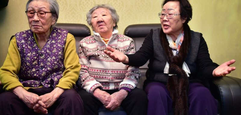 "Lee Yong-Soo (R), along with two other former South Korean ""comfort women"" Kim Bok-Dong (L) and Gil Won-Ok (C), voices criticism at talks with South Korean First Vice Foreign Minister Lim Sung-Nam (not pictured) during his visit to a shelter for women, who were forcibly recruited to work in Japanese wartime military brothels, in Seoul on December 29, 2015.  South Korean officials met with former ""comfort women"" to seek their support for a landmark deal with Japan, after criticism it does not properly atone for the treatment of women forced into WWII army brothels.  AFP PHOTO / POOL / JUNG YEON-JE / AFP / POOL / JUNG YEON-JE        (Photo credit should read JUNG YEON-JE/AFP/Getty Images)"