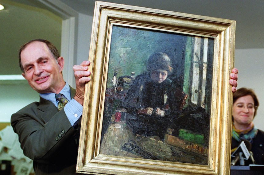 "NEW YORK, UNITED STATES:  Michael Loewenthal holds the painting ""The Seamstress"", 1883, by German painter Lesser Ury that was returned to Loewenthal as part of a settlement by the Holocaust Claims Processing Office of the New York State Banking Department 12 July, 1999, in New York. The settlement was with officials of Linz, Austria, who purchased the painting from a dealer in 1956. The painting was linked to ""tainted art"" obtained by Nazi officials through forced-sales from Jews. It originally belonged to Louis Loewenthal, the grandfather of Michael Loewenthal. AFP PHOTO  Stan HONDA (Photo credit should read STAN HONDA/AFP/Getty Images)"
