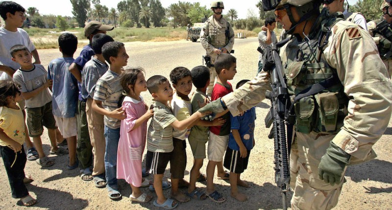 BAGHDAD, Iraq:  A Iraqi boy shakes hands with a US soldier during the Food Distribution Mission operated by Alpha Company, 425th Civil Affairs Company and 304th PYSOP Company of Task Force 4-64 Armor in Baghdad's Janain area, 29 August 2005.  AFP PHOTO/LIU Jin  (Photo credit should read LIU JIN/AFP/Getty Images)