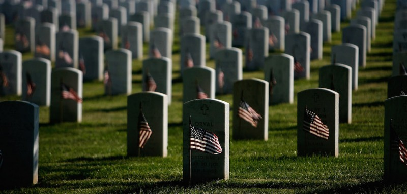 ARLINGTON, VA - MAY 24:  Small US flags wave in the wind after being placed in front of headstones at Arlington National Cemetery during the Flag-In Ceremony ahead of the Memorial Day weekend May 24, 2007 in Arlington, Virginia. It took approximately 3 hours for 1,300 soldiers, sailors and marines to put more than 300,000 flags in front of each of the gravestones at Arlington National Cemetery.  (Photo by Chip Somodevilla/Getty Images)