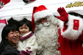 XIAN, CHINA - DECEMBER 21: (CHINA OUT) Customers pose with Nicholas from Finland, dressed as the Santa Claus during a promotion in a department store on December 21, 2008 in Xian of Shaanxi Province, China. Christmas continues to gain popularity each year in the Chinese consumer culture.  (Photo by China Photos/Getty Images)