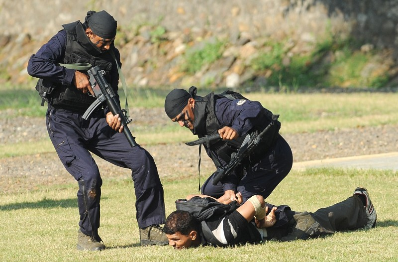 Indian Force One special commando forces apprehend a man during a simulated terrorist attack at the elite unit's inaugural function in Mumbai on November 24, 2009. The 256-strong unit Force One, modelled on India's National Security Guard, is designed as a quick response team for counter-terrorism following criticism that Mumbai police was under-equipped, ill-trained and lacking manpower to tackle the heavily-armed gunmen during the November 26, 2008 terror attacks. AFP PHOTO/ Indranil MUKHERJEE (Photo credit should read INDRANIL MUKHERJEE/AFP/Getty Images)