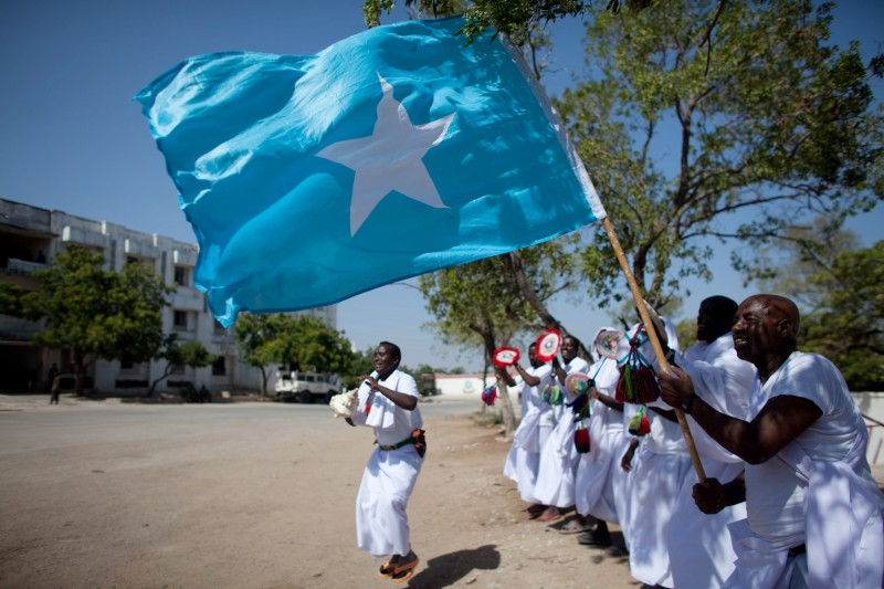 A Somali man holds a Somali flag while others dance during a ceremony feting the first year of President Sharif Sheikh Ahmed's shaky rule at Villa Somalia, the presidential palace, lies on the ground in Mogadishu on January 28, 2010. Al Qaeda-linked Somali insurgents on January 29 rained mortar rounds on a ceremony feting the first year of President Sharif Sheikh Ahmed's shaky rule after a night of fighting that killed at least nine. AFP PHOTO / YASUYOSHI CHIBA (Photo credit should read YASUYOSHI CHIBA/AFP/Getty Images)