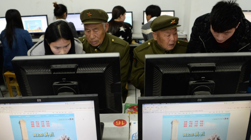 This picture taken on April 2, 2015 shows a group of Chinese university students help elderly People's Liberation Army (PLA) veterans pay their respects online to fallen comrades on Qingming festival in Bozhou, China's Anhui province.  Qingming is a traditional Chinese festival, also called Tomb Sweeping Day where families gather to commemorate and show respects to their ancestors.       CHINA OUT      AFP PHOTO        (Photo credit should read STR/AFP/Getty Images)