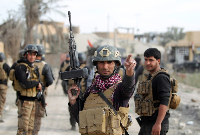 TOPSHOT - Members of Iraq's elite counter-terrorism service secure on December 27, 2015 the Hoz neighbourhood in central Ramadi, the capital of Iraq's Anbar province, about 110 kilometers west of Baghdad, during military operations conducted by Iraqi pro-government forces against the Islamic State (IS) jihadist group. Jihadist fighters abandoned their last stronghold in Ramadi today, bringing Iraqi federal forces within sight of their biggest victory since last year's massive offensive by the Islamic State group. AFP PHOTO / AHMAD AL-RUBAYE / AFP / AHMAD AL-RUBAYE        (Photo credit should read AHMAD AL-RUBAYE/AFP/Getty Images)