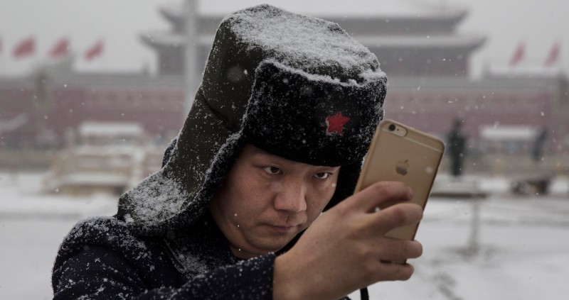 BEIJING, CHINA - NOVEMBER 22:  A Chinese man takes a selfie in a snow covered Tiananmen Square during a snowfall on November 22, 2014 in Beijing, China. China's capital and other parts of northern China had its second snowfall of the year Sunday.  (Photo by Kevin Frayer/Getty Images)