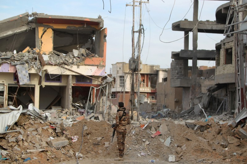 TOPSHOT - A member of Iraqi pro-government forces stands amid the rubble of destroyed buildings in the Hoz neighbourhood in central Ramadi, the capital of Iraq's Anbar province, about 110 kilometers west of Baghdad, on December 27, 2015 during military operations conducted by Iraqi pro-government forces against the Islamic State (IS) jihadist group. Jihadist fighters abandoned their last stronghold in Ramadi today, bringing Iraqi federal forces within sight of their biggest victory since last year's massive offensive by the Islamic State group. AFP PHOTO / AHMAD AL-RUBAYE / AFP / AHMAD AL-RUBAYE        (Photo credit should read AHMAD AL-RUBAYE/AFP/Getty Images)