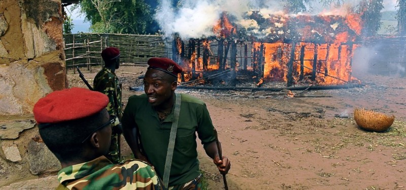 Soldiers run from a house set afire by protestors opposed to the Burundian president's bid to stand for a third term in Butagazwa, Mugongomanga, some 30km east of Bujumbura, on June 5, 2015. The house belonged to Diodeme Ndabahinyuye, vice chairman of the National Council for the Defense of DemocracyForces for the Defense of Democracy (CNDD-FDD) ruling party Mugongomanga community division. Police in Burundi on June 5 shot dead a protester in the capital amid renewed demonstrations against President Pierre Nkurunziza, witnesses and a local official said.  AFP PHOTO / CARL DE SOUZA        (Photo credit should read CARL DE SOUZA/AFP/Getty Images)