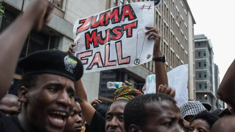 Students from Johannesburg and Witts universities, hold placards reading 'Zuma must fall', as they arrive at the African National Congress ruling party (ANC) headquarters, on October 22, 2015, in Johannesburg, to protest against university fee hikes. University activism has been increasing this year as students vent their anger over the limited racial transformation in education since racist white-minority rule ended with Nelson Mandela's election in 1994. Many students says higher fees -- which could rise by 10 percent a year -- will further prevent poorer black youths gaining university education. AFP PHOTO / MUJAHID SAFODIEN        (Photo credit should read MUJAHID SAFODIEN/AFP/Getty Images)