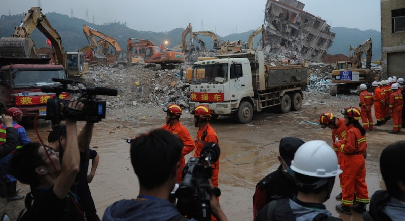 Journalists (bottom) prevented from moving any closer to the site by security personnel, shoot outside the site of landslide that hit an industrial park in Shenzhen in south China's Guangdong province on December 22, 2015. Rescuers struggled to claw away a massive mound of mud engulfing an industrial district in China on December 22 in a desperate bid to find survivors among 76 missing people following a landslide that occurred despite multiple warnings.  CHINA OUT   AFP PHOTO / STR / AFP / STR        (Photo credit should read STR/AFP/Getty Images)