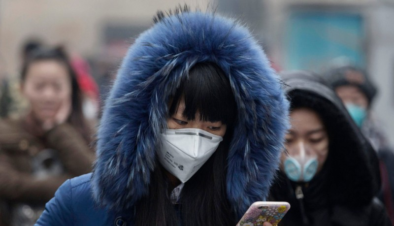 """BEIJING, CHINA - DECEMBER 09:  A  Chinese woman wears a mask as she walks to work during heavy pollution on December 9, 2015 in Beijing, China. The Beijing government issued a """"red alert"""" Sunday for the first time since new standards were introduced earlier this year as the city and many parts of northern China were shrouded in heavy pollution. Levels of PM 2.5, considered the most hazardous, crossed 400 units in Beijing, lower then last week, but still nearly 20 times the acceptable standard set by the World Health Organization. The governments of more than 190 countries are meeting in Paris to set targets on reducing carbon emissions in an attempt to forge a new global agreement on climate change.  (Photo by Kevin Frayer/Getty Images)"""