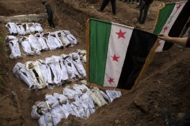 """Syrian mourners wave the pre-Baath Syrian flag, now used by the Free Syrian Army, over the bodies of civilians, who were executed and dumped in the Quweiq river, during their burial at a park now renamed """"Martyrs of the River"""" park in the Bustan al-Qasr district of the northern city of Aleppo on January 31, 2013. The bodies of dozens of young men, all executed with a single gunshot, were found in the river this week, adding to the grim list of massacres committed during Syria's 22-month conflict. AFP PHOTO/JM LOPEZ        (Photo credit should read JM LOPEZ/AFP/Getty Images)"""
