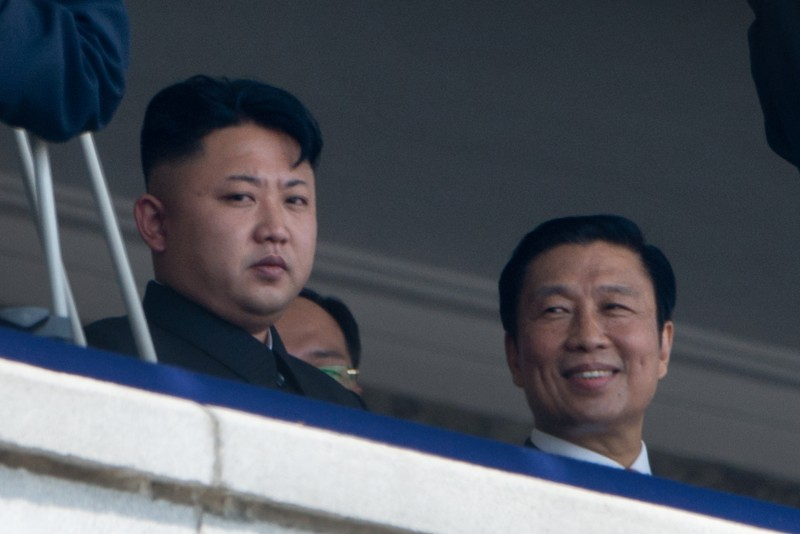 North Korean leader Kim Jong-Un (L) sits with China's Vice President Li Yuanchao (R) during a military parade at Kim Il-Sung square marking the 60th anniversary of the Korean war armistice in Pyongyang on July 27, 2013.  North Korea mounted its largest ever military parade on July 27 to mark the 60th anniversary of the armistice that ended fighting in the Korean War, displaying its long-range missiles at a ceremony presided over by leader Kim Jong-Un.  AFP PHOTO / Ed Jones        (Photo credit should read Ed Jones/AFP/Getty Images)