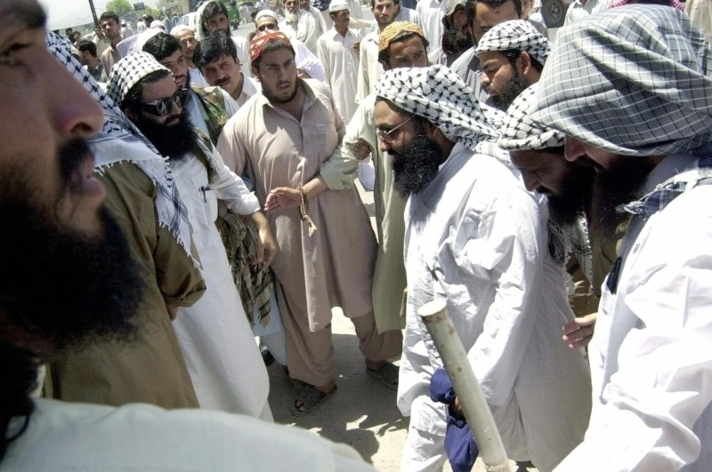Mulana Masood Azhar (3rd R), head of an outlawed militant organization of Jaish-e-Mohammad makes his way towards a mosque in Peshawar 30 May 2003. Azhar, who was prevented from speaking at press conference, delivered Friday prayer sermon in which he hailed Al-Qaeda chief Osama bin Laden and the Taliban's spiritual leader Mullah Omar as heroes. AFP PHOTO/Tariq MAHMOOD  (Photo credit should read TARIQ MAHMOOD/AFP/Getty Images)
