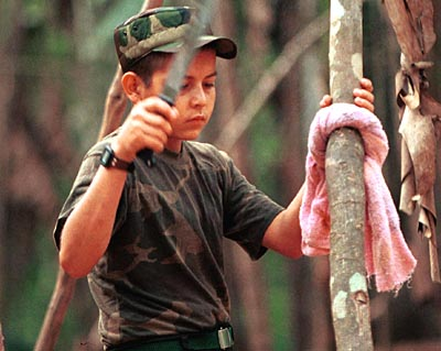 WORLD PAGE SUNDAY FUTURE: Colombia-FARC project: After sharpening his machete, a young FARC rebel tests the blade on a tree in a rebel camp near La Sombra in the dmz. Thousands  of FARC troops are teenagers. credit: Marcelo SalinasSpecial to Chronicle